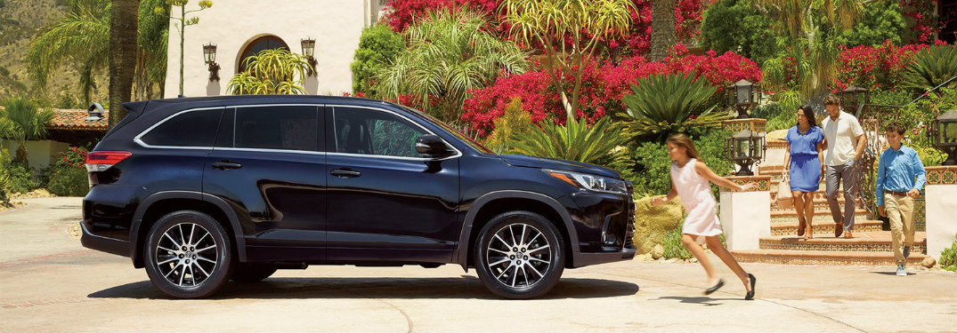 2018 Toyota Highlander Hybrid with family running toward it