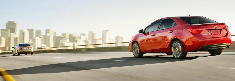 2019 Toyota Corolla driving on highway toward big city