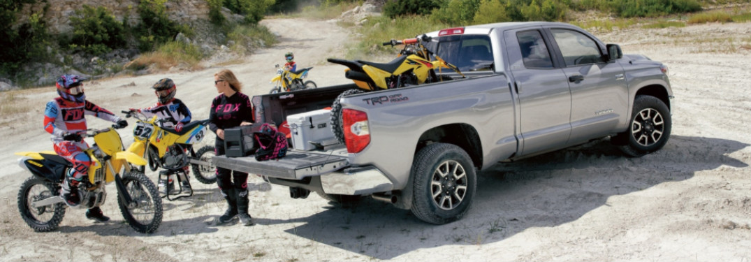 2018 Toyota Tundra with dirt bikes in truck bed and family surrounding