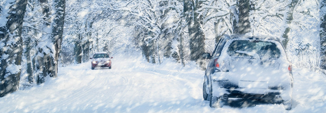 Two cars headed in opposite directions on a snow-covered road in winter