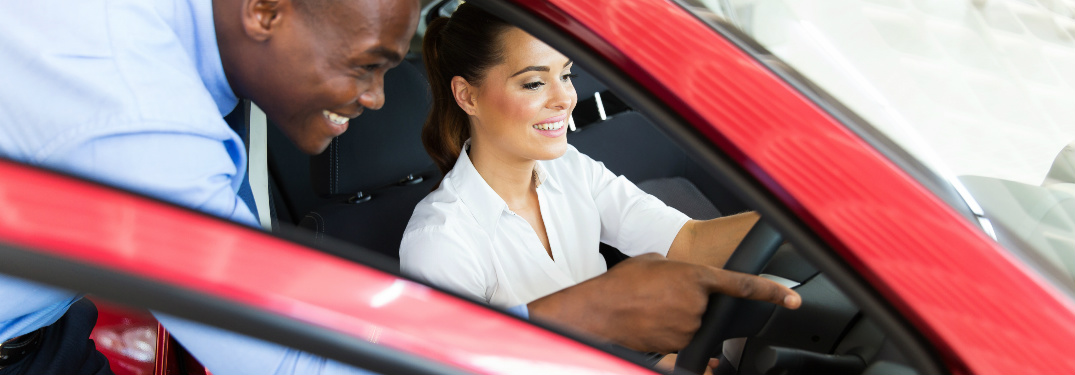 Car salesman pointing out vehicle features to car shopper
