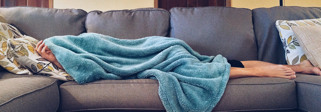 Someone laying on the couch underneath a blanket