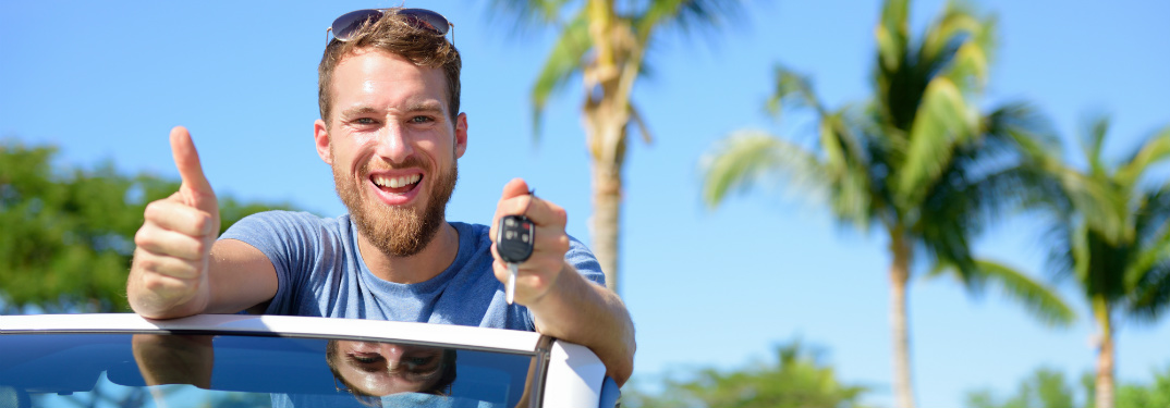 Man holding car keys and giving a thumbs up
