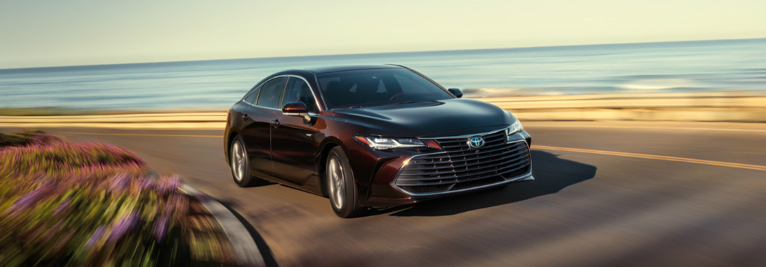 2019 Toyota Avalon in Opulent Amber driving on an oceanfront road