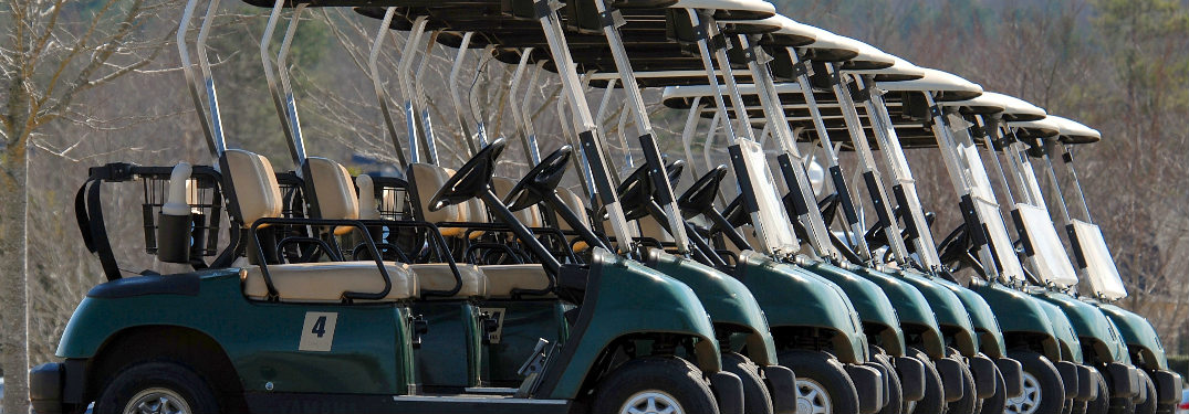 Green golf carts lined up in a row