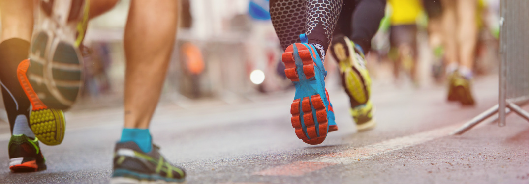 Close up show of a group of runners legs while they are running down the road
