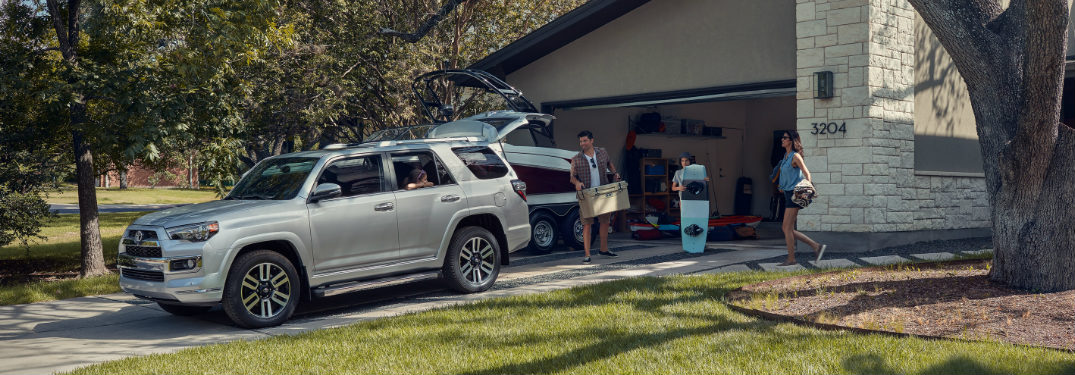 Family loading a cooler and wakeboard into the back of a 2019 Toyota 4Runner