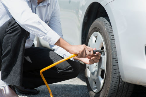Driver checking tire pressure