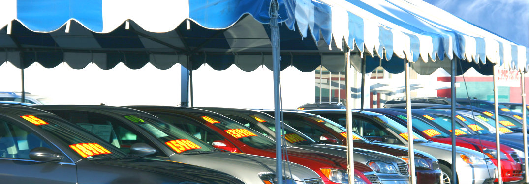 Used cars parked under a blue and white striped tent