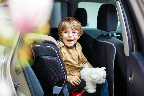 young boy climbing out of his car seat with a stuffed animal