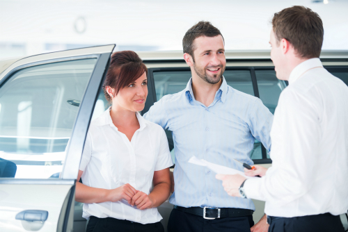 young couple talking to a car salesman at the dealership