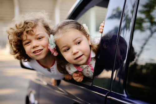 kids sticking their heads out of a car