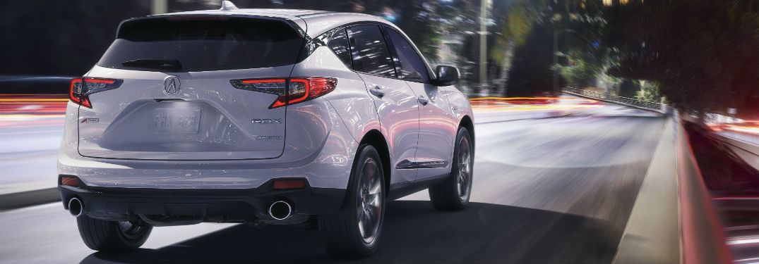 2019 Acura RDX Pricing and Mileage Information with an image of a 2019 Acura RDX with Advance Package in Lunar Silver Metallic driving down a road in a city at night