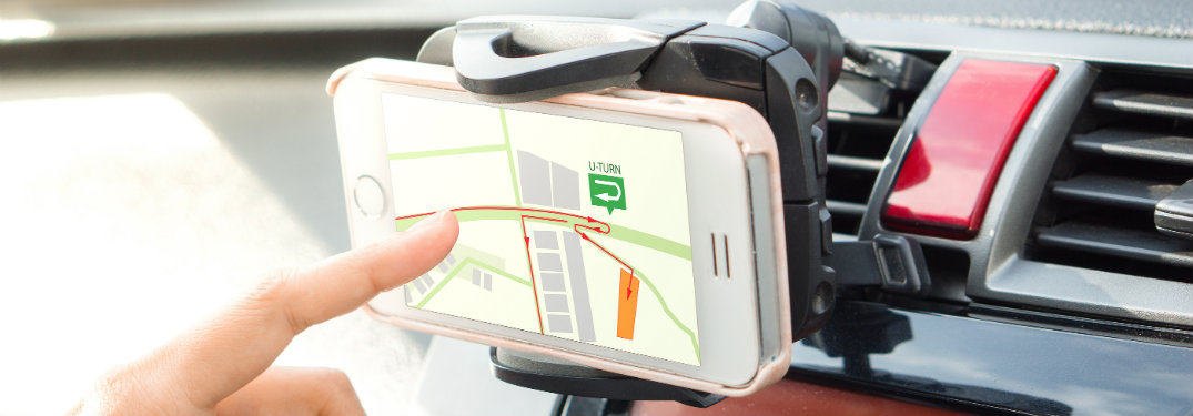 Index finger pressing smartphone GPS screen with phone in a phone mount.