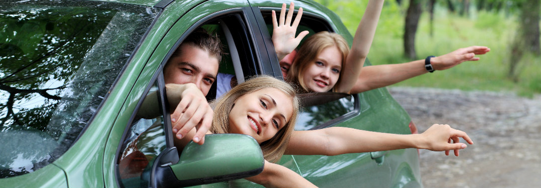 people crammed into a green car for a road trip