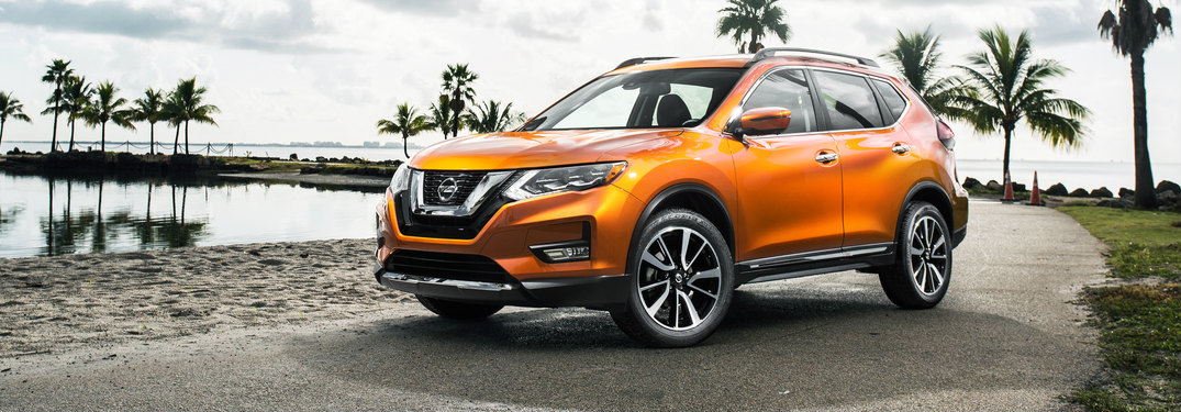 orange 2017 Nissan Rogue with palm trees behind it