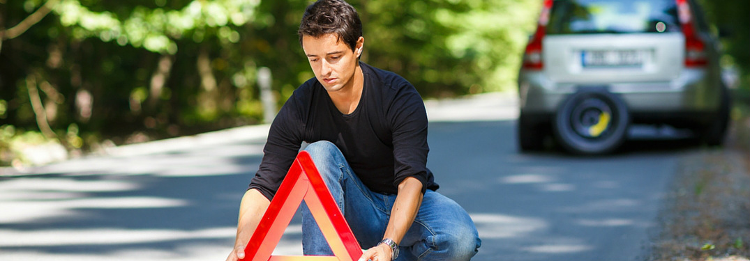man setting up road triangle behind broken down car