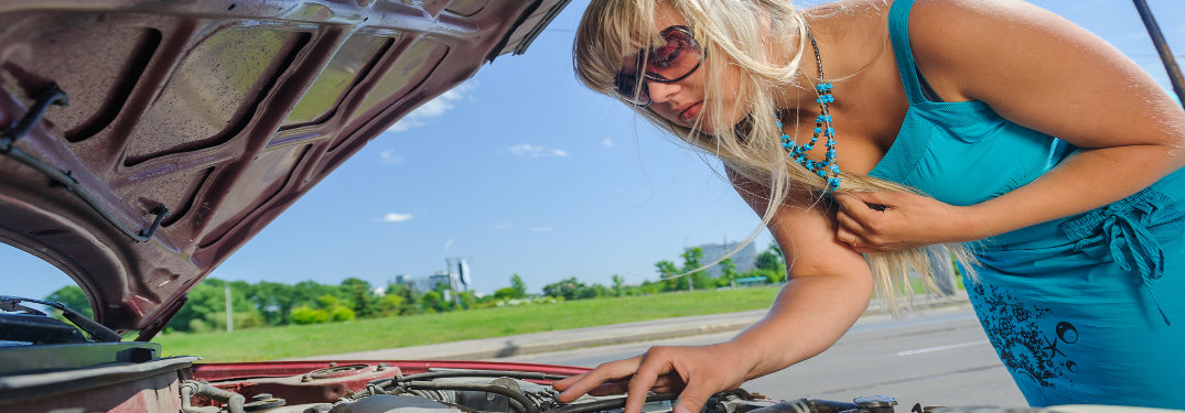 blonde woman looking under hood of broken-down car