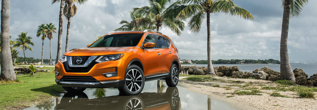 orange 2018 Nissan Rogue sitting in front of palm trees on a beach