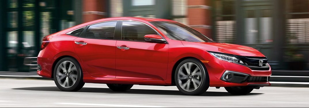 Red 2019 Honda Civic cruises down a city street. Exterior side/front angled view.