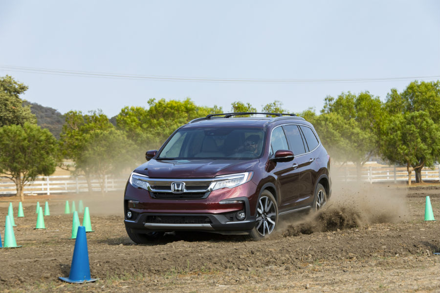 A photo of the 2020 Honda Pilot driving through mud.