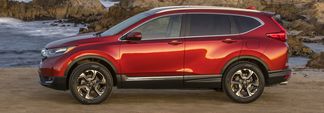 side view of red 2018 honda cr-v on cliff overlooking ocean