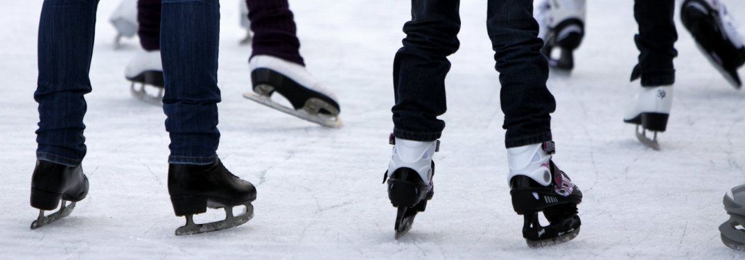 Close-up-of-peoples-skates-while-they-ice-skate