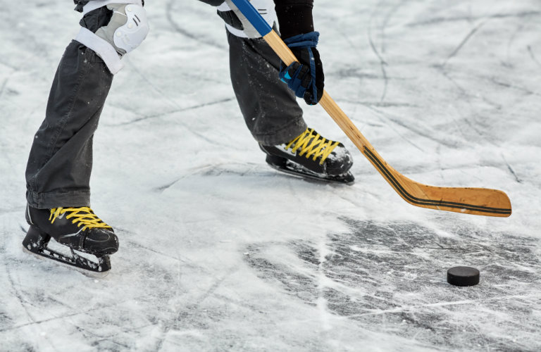 Legs-of-hockey-player-about-to-hit-puck