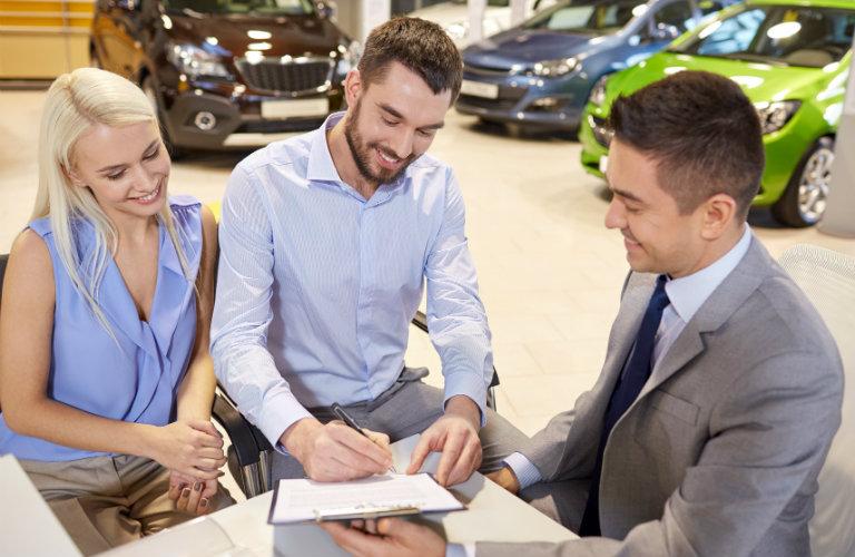 Man-signing-paperwork-at-car-dealership