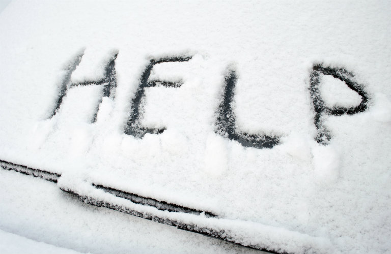 Snow-covered-windshield-wiper-with-help-written-in-snow