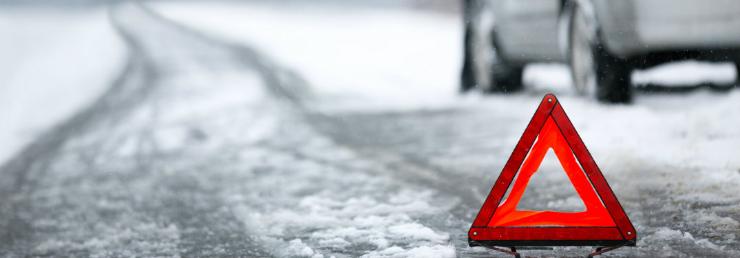 Warning-triangle-on-snow-covered-slushy-road