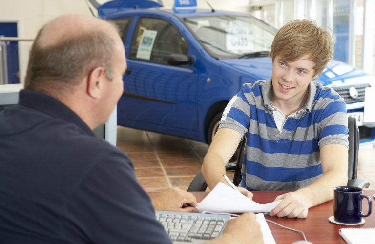 Young-man-filling-out-paperwork-with-car-salesman