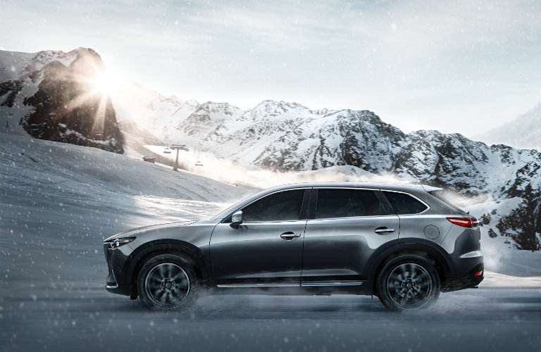 2018-Mazda-CX-9-driving-on-snowy-road-in-front-of-mountains