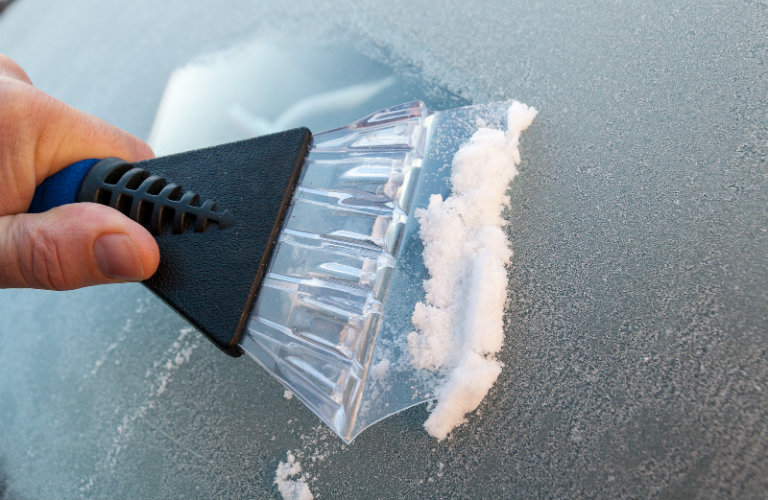 Close-up-of-ice-scraper-scraping-off-windshield