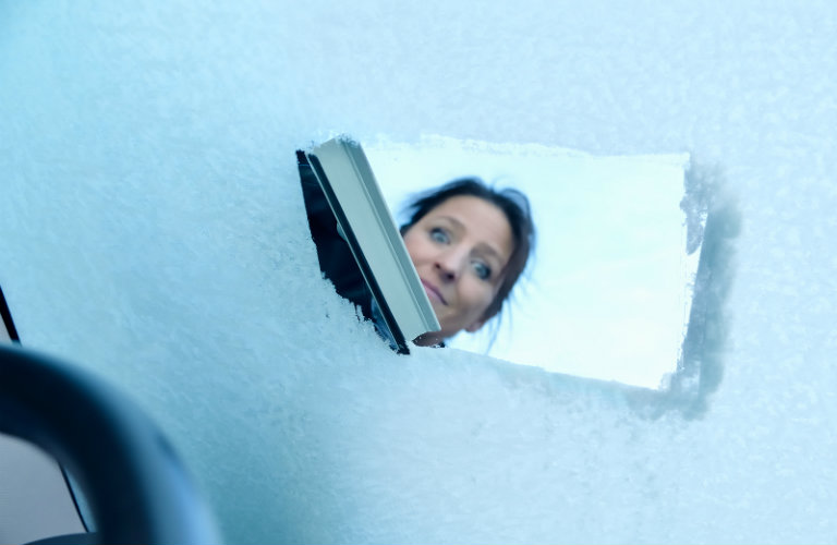 Woman-scraping-off-ice-on-windshield