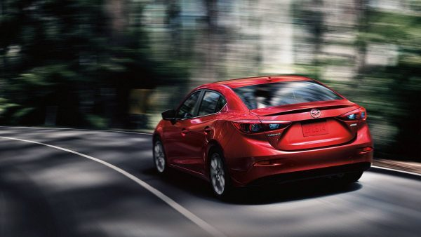 2018 Mazda3 sedan driving on a wooded highway