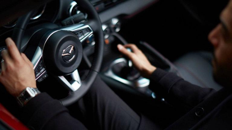 Close-up-of-driver-and-steering-wheel-inside-2018-Mazda-MX-5-Miata-RF