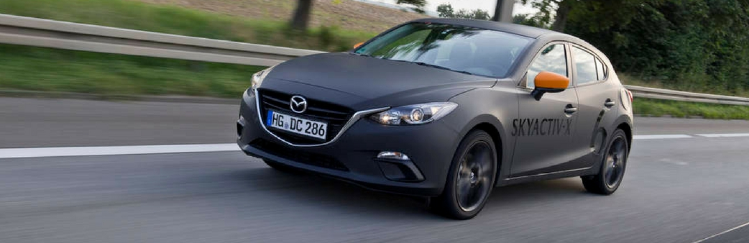 2019 Mazda3 driving down a road.