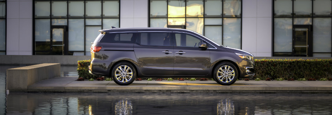 dark gray kia sedona parked by water