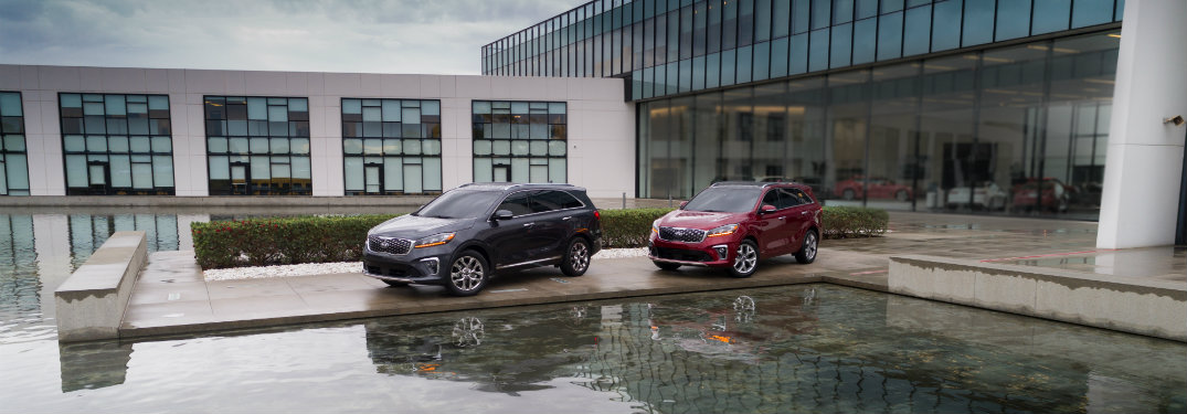 gray and red kia sorento vehicles parked by water and building