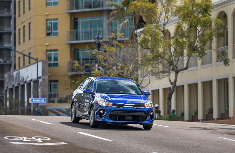 2018 Kia Rio in blue driving down a city hill