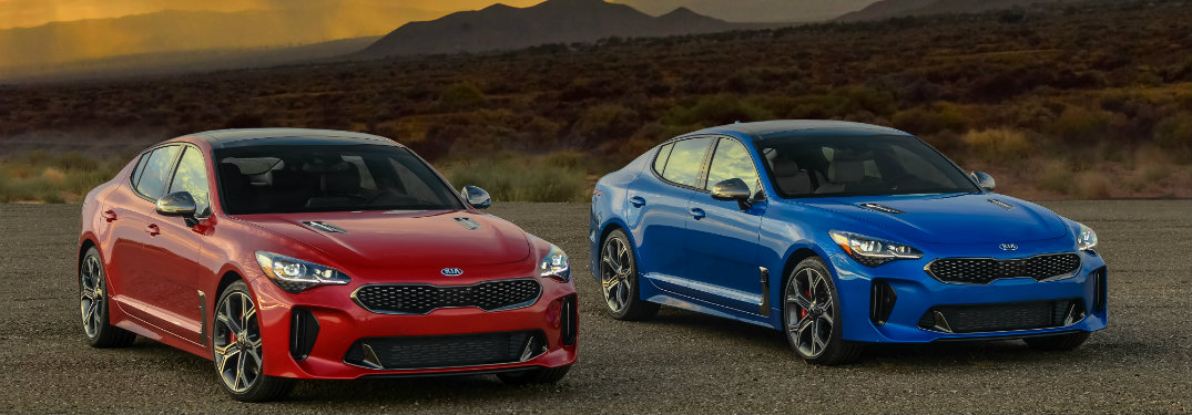blue and red kia stingers parked by each other