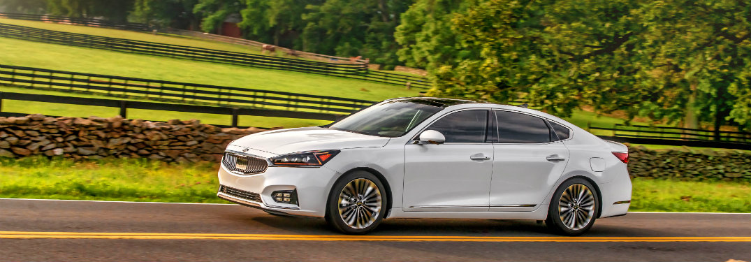 left side view of white kia cadenza driving by field