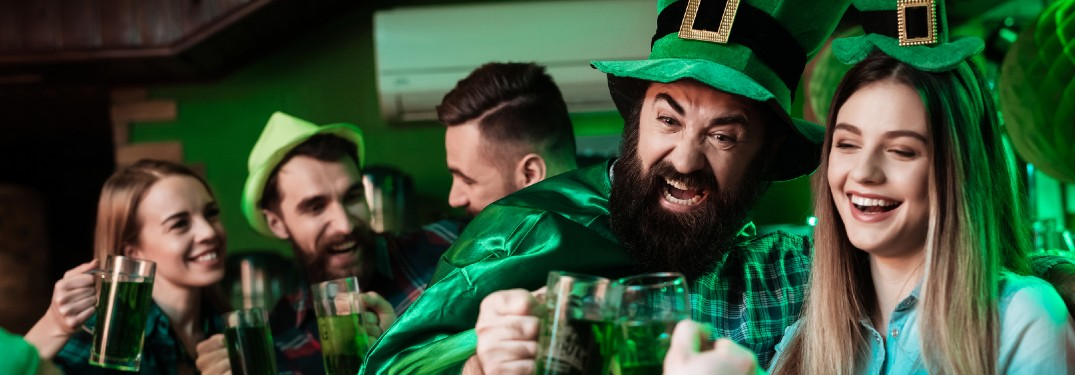 Friends having fun in a tavern wearing green clothes during St. Patrick's Day.