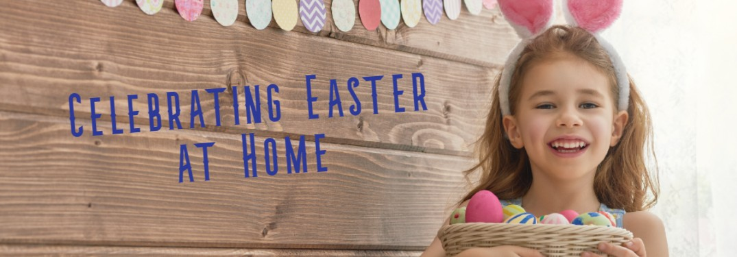 """A picture of a little girl with bunny ears indoors smiling with the caption along the wooden wall saying """"Celebrating Easter at Home""""."""