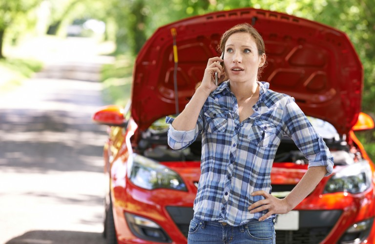 A redheaded woman standing in front of her vehicle calling for help.