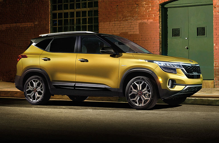 A yellow 2021 Kia Seltos parked in a lighted alley.
