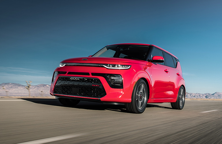 A front and side view of a 2020 Kia Soul GT-Line Turbo driving down an open road.