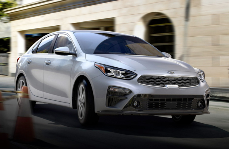 A gray 2020 Kia Forte driving around a safety cone in a city.