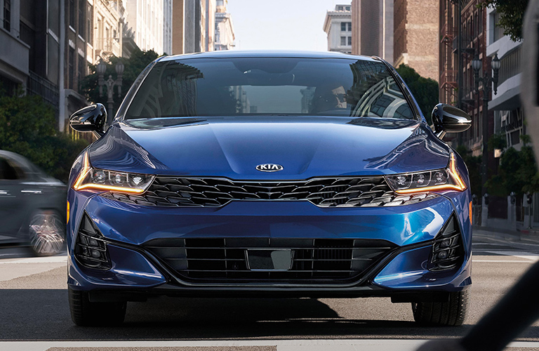 The front exterior of a blue 2021 Kia K5.